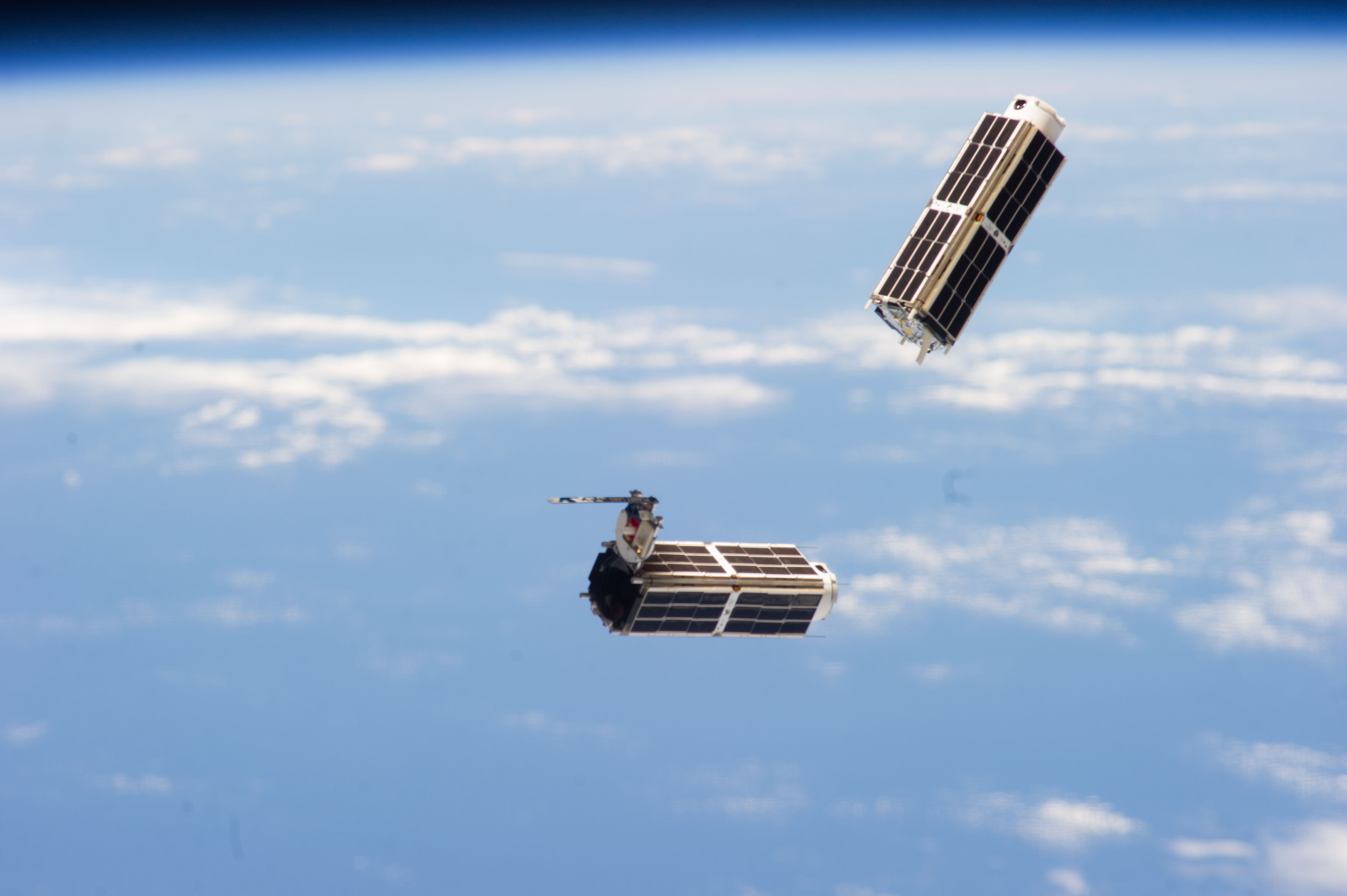 Doves launched from ISS float against Earth horizon.jpg